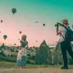 a couple taking photos of hot air balloons