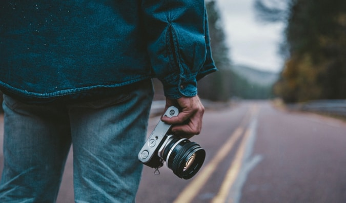 A man holding a camera while standing on a road