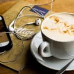a latte and ipod on the table while someone listens to a podcast