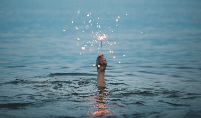 A man holding a sparkler while under water